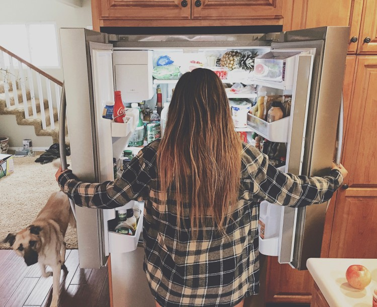 Girl looking for coffee in the fridge